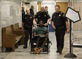 In this May 12, 2011 photo, accused rapist and murderer Isaiah Kalebu, lower center, is taken in a wheeled restraint chair through a hallway at the King County Courthouse following a court hearing in Seattle. Judge Michael C. Hayden has taken the unusual step of tentatively barring Kalebu from attending his own trial when opening statements begin in King County Superior Court, Monday, June 6, 2011, because of outbursts during pre-trial hearings. Instead, Kalebu will be able to watch the proceedings via closed-circuit television from a nearby courtroom. (AP Photo/Ted S. Warren)