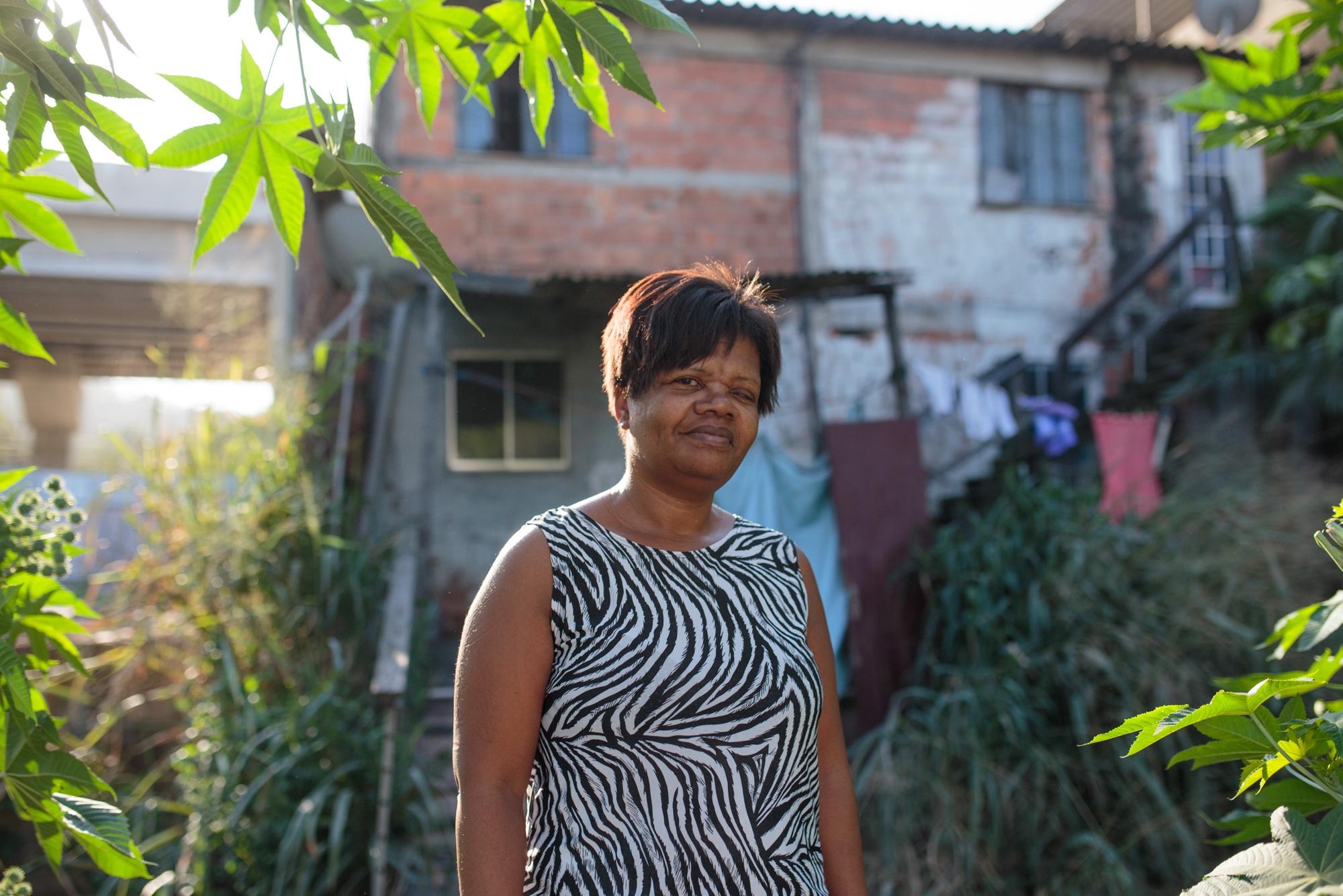 Glória Dionéia Rodrigues de Mattos, de 52 anos, em frente à sua casa, com a Transolímpica ao fundo.